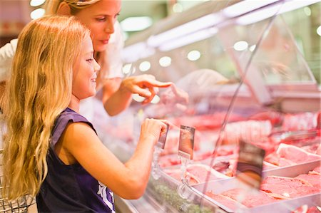 Mother and daughter at butcher counter Stock Photo - Premium Royalty-Free, Code: 649-06717222
