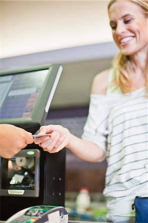 Woman paying with credit card in store Stock Photo - Premium Royalty-Free, Code: 649-06717231