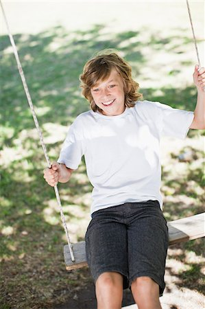 Boy playing on swing in park Stock Photo - Premium Royalty-Free, Code: 649-06717244