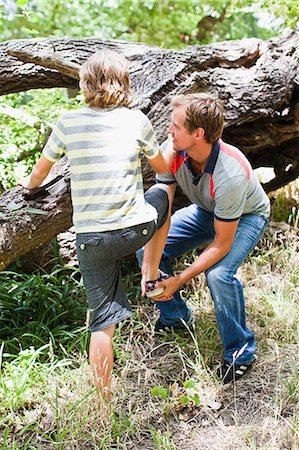 Father helping son over fallen tree Stock Photo - Premium Royalty-Free, Code: 649-06717265