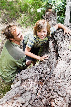 Father helping son over fallen tree Stock Photo - Premium Royalty-Free, Code: 649-06717266