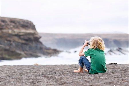 Boy using binoculars on beach Stock Photo - Premium Royalty-Free, Code: 649-06717326