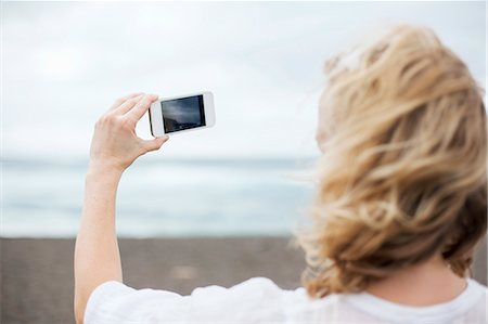 Woman taking cell phone picture on beach Stock Photo - Premium Royalty-Free, Code: 649-06717328