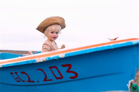 side view of person rowing in boat - Toddler girl sitting in boat on beach Stock Photo - Premium Royalty-Free, Code: 649-06717330