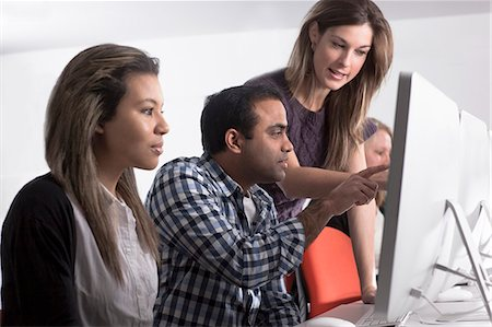 Teacher helping students use computers Stock Photo - Premium Royalty-Free, Code: 649-06717371