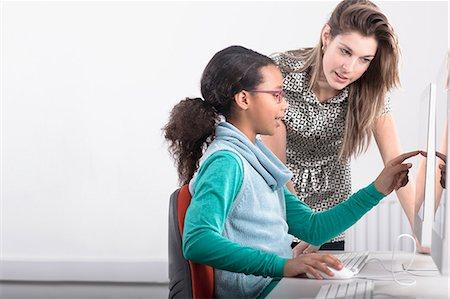 Teacher helping student use computer Stock Photo - Premium Royalty-Free, Code: 649-06717382