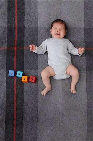 Baby boy crying on bed Stock Photo - Premium Royalty-Free, Code: 649-06717446