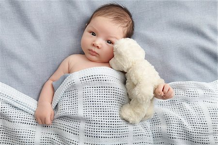 Baby boy and teddy bear laying in bed Stock Photo - Premium Royalty-Free, Code: 649-06717458