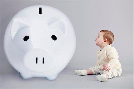 Baby girl examining large piggy bank Stock Photo - Premium Royalty-Free, Code: 649-06717461