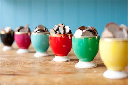 Egg cups full of money on desk Stock Photo - Premium Royalty-Free, Code: 649-06717484
