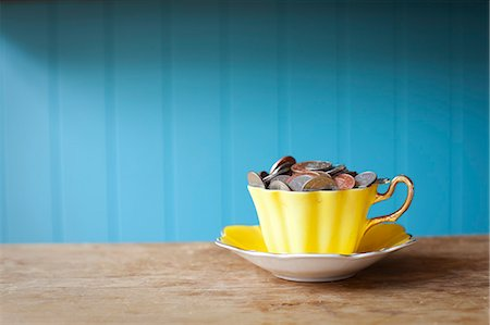 Teacup full of money on desk Stock Photo - Premium Royalty-Free, Code: 649-06717481