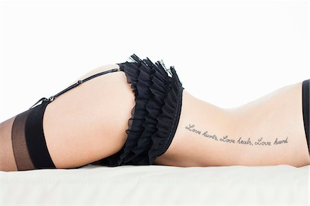 Woman wearing lingerie on bed Stock Photo - Premium Royalty-Free, Code: 649-06717503