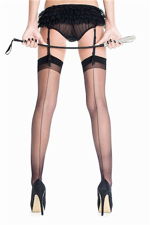 Woman in lingerie holding riding crop Stock Photo - Premium Royalty-Free, Code: 649-06717511