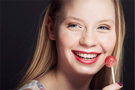 Smiling woman eating lollipop Stock Photo - Premium Royalty-Free, Code: 649-06717550