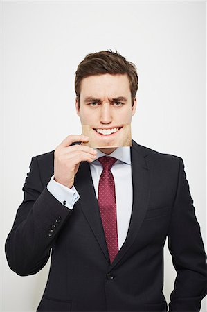 dece11 - Businessman holding angry picture over his face Stock Photo - Premium Royalty-Free, Code: 649-06717566