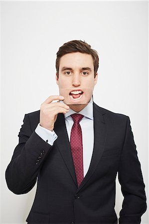 dece11 - Businessman holding picture over his mouth Stock Photo - Premium Royalty-Free, Code: 649-06717567
