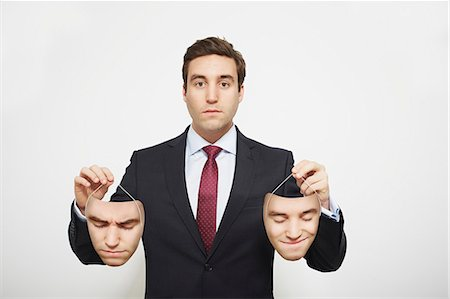 person silhouette face - Businessman holding masks Stock Photo - Premium Royalty-Free, Code: 649-06717562