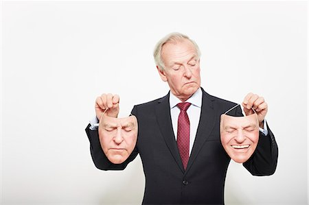 person silhouette face - Businessman holding masks Stock Photo - Premium Royalty-Free, Code: 649-06717591
