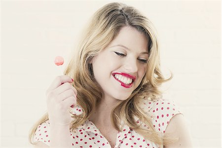 Smiling woman eating lollipop Stock Photo - Premium Royalty-Free, Code: 649-06717608