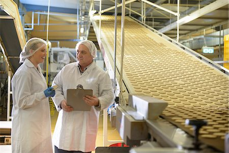 people working in factory - Workers talking in biscuit factory Stock Photo - Premium Royalty-Free, Code: 649-06717663