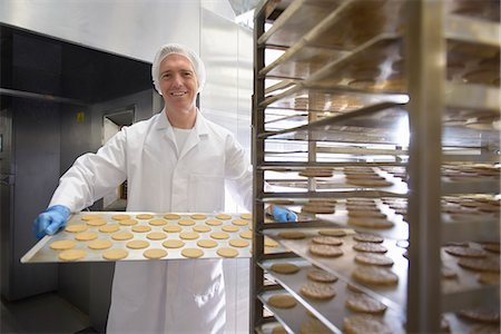 Worker baking biscuits in factory Stock Photo - Premium Royalty-Free, Code: 649-06717687
