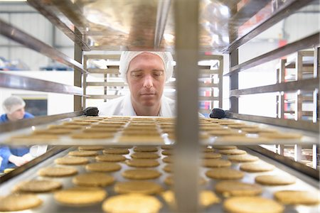 focus on background - Worker examining biscuits in factory Stock Photo - Premium Royalty-Free, Code: 649-06717690