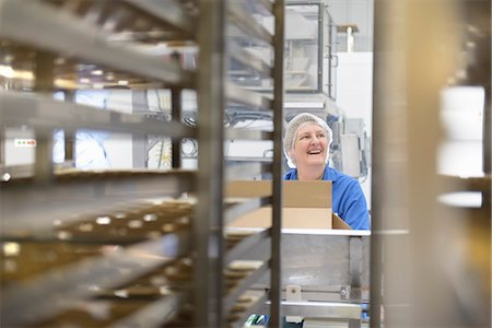 focus on background - Worker packing in biscuit factory Stock Photo - Premium Royalty-Free, Code: 649-06717691