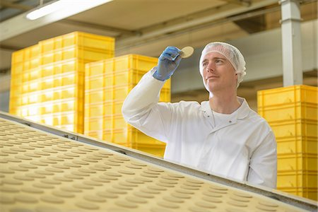 Worker examining biscuit in factory Stock Photo - Premium Royalty-Free, Code: 649-06717702