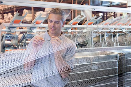 Worker examining loom in textile mill Stock Photo - Premium Royalty-Free, Code: 649-06717735
