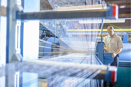 production - Worker examining loom in textile mill Stock Photo - Premium Royalty-Free, Code: 649-06717736