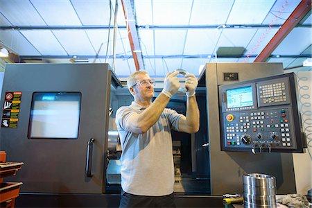 Engineer examining part in factory Stock Photo - Premium Royalty-Free, Code: 649-06717731