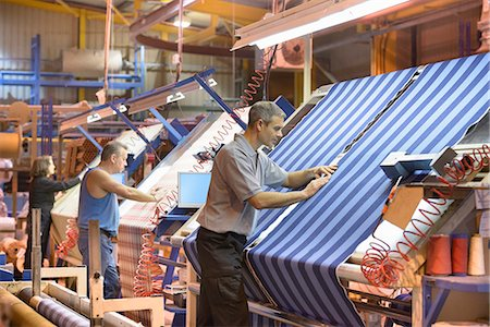 Worker examining loom in textile mill Stock Photo - Premium Royalty-Free, Code: 649-06717744