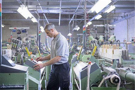 production - Worker using loom in textile mill Stock Photo - Premium Royalty-Free, Code: 649-06717759