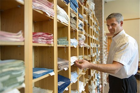 Worker examining fabric in textile mill Stock Photo - Premium Royalty-Free, Code: 649-06717765