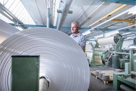 Worker examining fabric in textile mill Stock Photo - Premium Royalty-Free, Code: 649-06717784