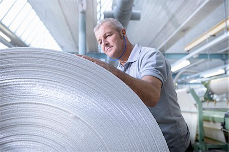 Worker examining fabric in textile mill Stock Photo - Premium Royalty-Free, Code: 649-06717785