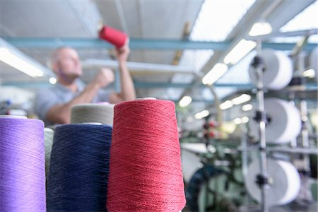 Worker examining thread in textile mill Stock Photo - Premium Royalty-Free, Code: 649-06717789
