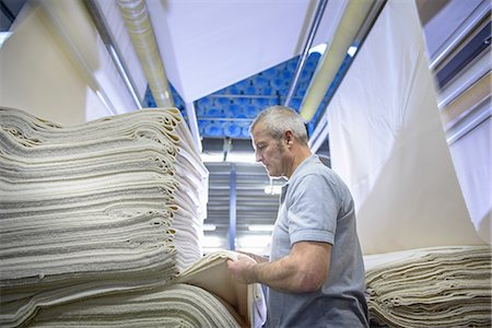 Worker examining fabric in textile mill Stock Photo - Premium Royalty-Free, Code: 649-06717794