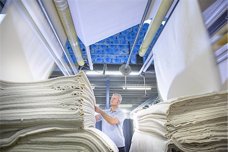 Worker examining fabric in textile mill Stock Photo - Premium Royalty-Free, Code: 649-06717793