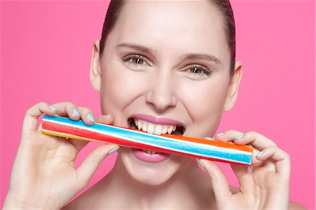 Smiling woman biting candy Stock Photo - Premium Royalty-Free, Code: 649-06717827