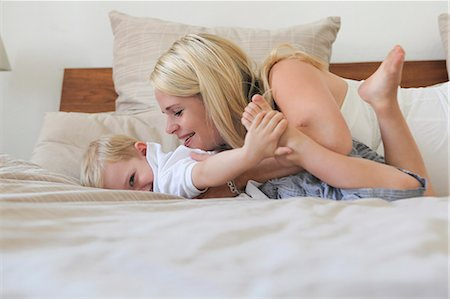 Mother and son playing on bed Stock Photo - Premium Royalty-Free, Code: 649-06717858
