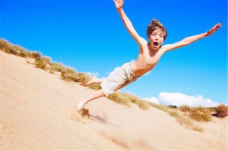 preteen boy shirtless - Boy falling on sand dune Stock Photo - Premium Royalty-Free, Code: 649-06812029