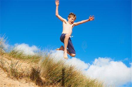 preteen boy shirtless - Boy jumping on beach Stock Photo - Premium Royalty-Free, Code: 649-06812035