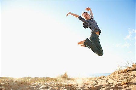 Teenage girl jumping on beach Stock Photo - Premium Royalty-Free, Code: 649-06812039