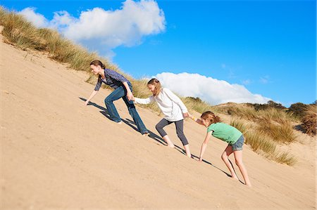 Three girls climbing up sand dune Stock Photo - Premium Royalty-Free, Code: 649-06812030