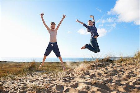 Boy and teenage girl jumping on beach Stock Photo - Premium Royalty-Free, Code: 649-06812049