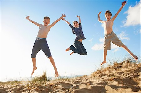 Boys and teenage girl jumping on beach Stock Photo - Premium Royalty-Free, Code: 649-06812050