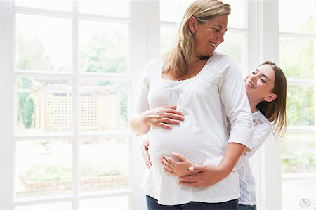 portrait of pregnant woman - Pregnant mother with teenage daughter by window Stock Photo - Premium Royalty-Free, Code: 649-06812075