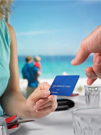 Woman paying beach restaurant with credit card Stock Photo - Premium Royalty-Free, Code: 649-06812097