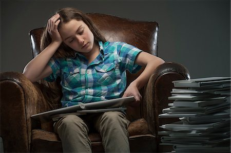 person overwhelmed stresss - Girl sitting in leather armchair with piles of books Stock Photo - Premium Royalty-Free, Code: 649-06812236